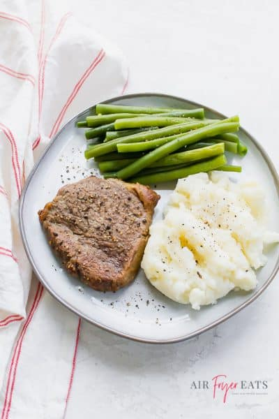 steak with mashed potatoes and green beans on a plate over a red and white striped towel