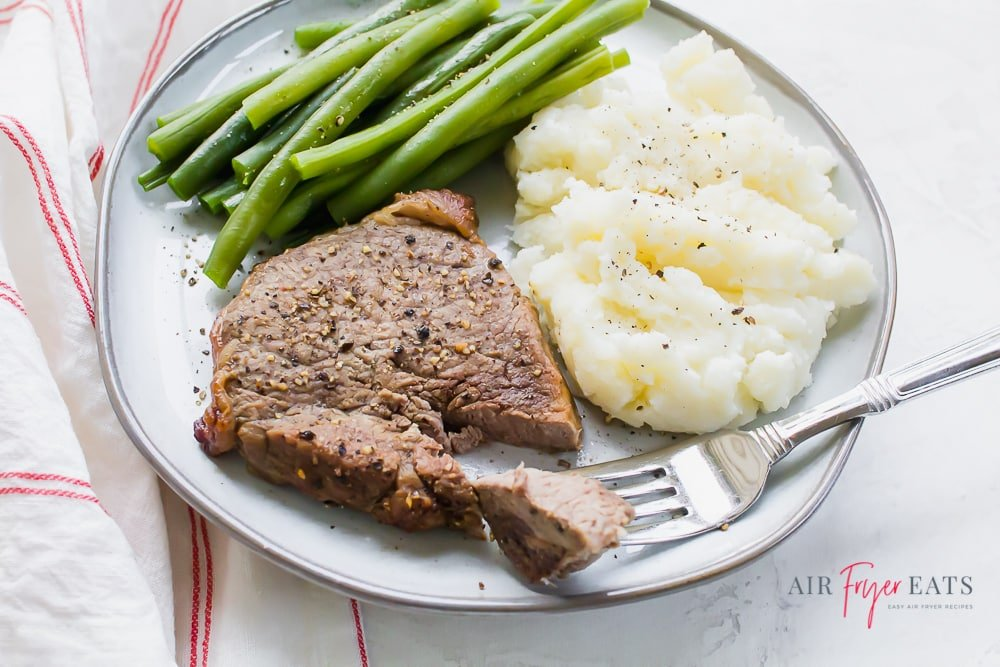 a fork piercing a piece of steak from a steak filet on a plate with mashed potatoes and green beans