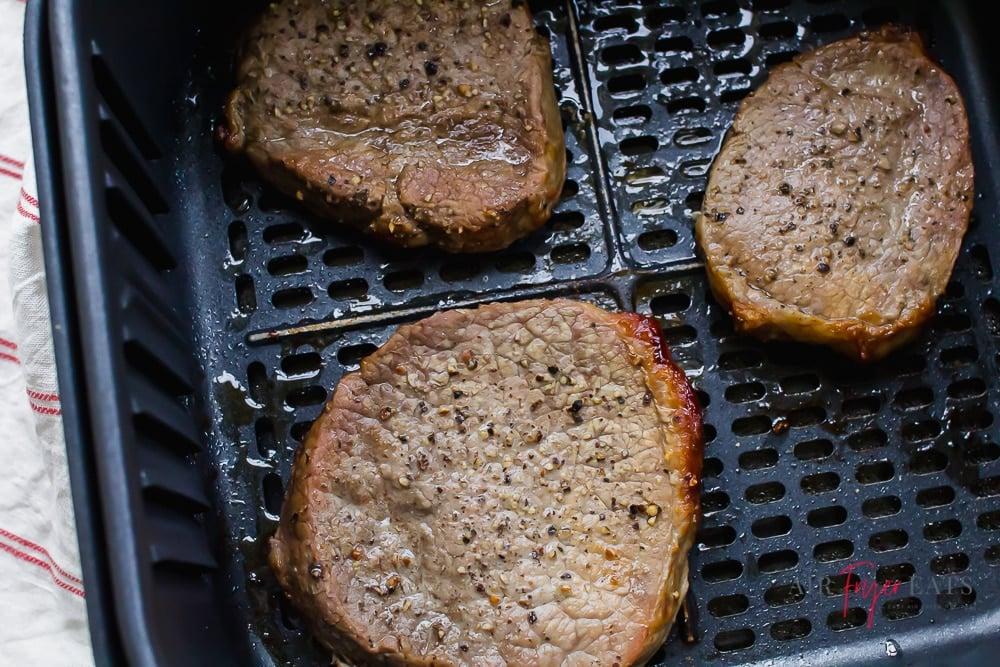 three filets of steak in a black air fryer basket