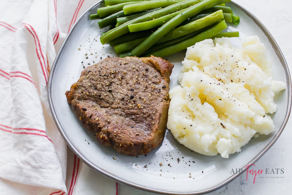 a small cut of steak on a plate with a pile of mashed potatoes and green beans