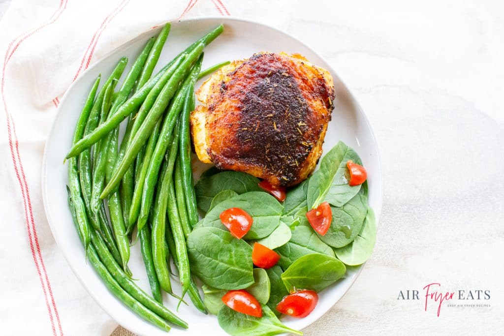 a chicken thigh with green beans and a small salad on a white plate