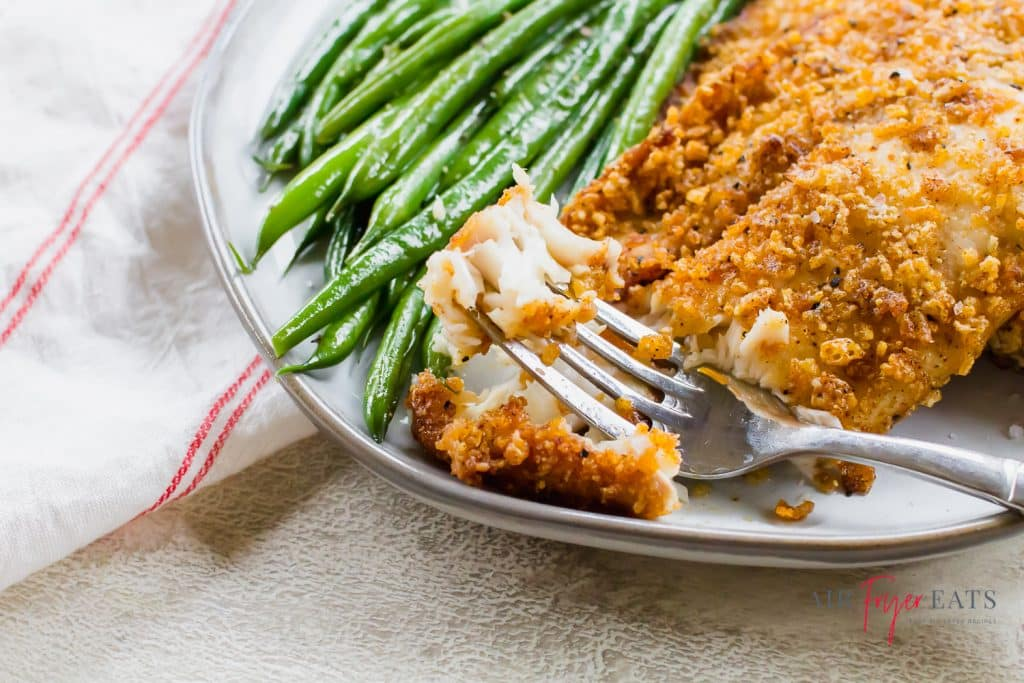 a piece of cooked tilapia on a fork with a side of green beans on a white plate