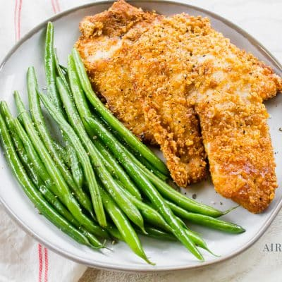 breaded fish with green beans on a white plate