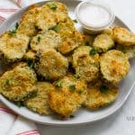 fried round slices of pickles garnished with green herbs on a white plate