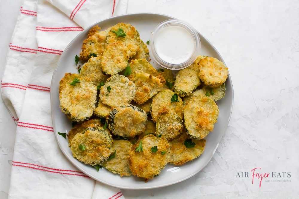 a plate of fried pickle slices with ranch dipping sauce