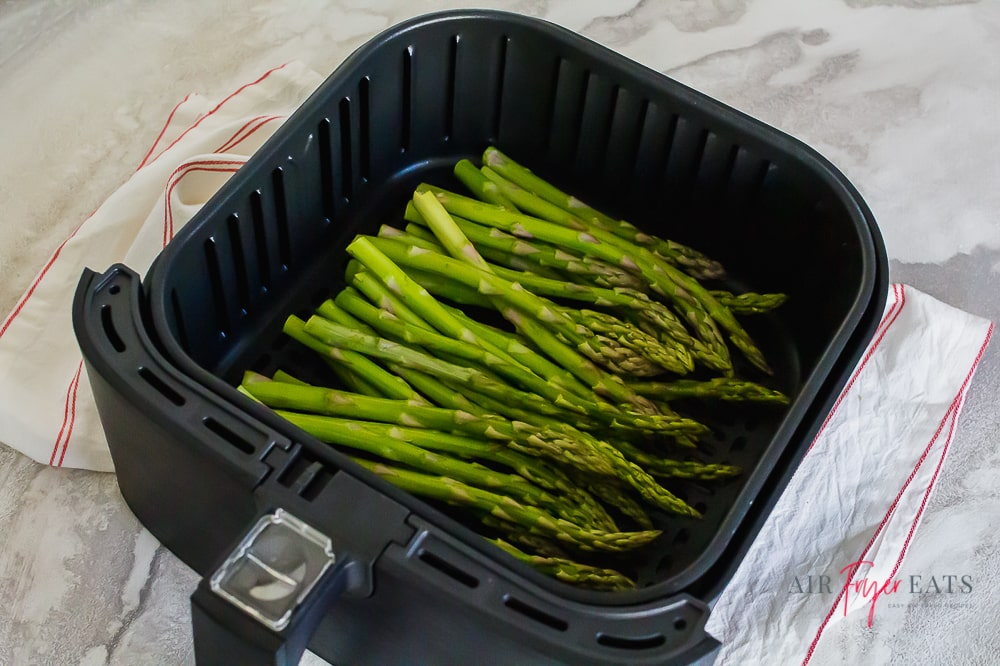 Raw asparagus sits in an air fryer basket on a countertop