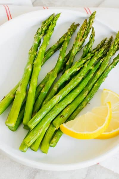 Asparagus and lemon wedges on a white plate