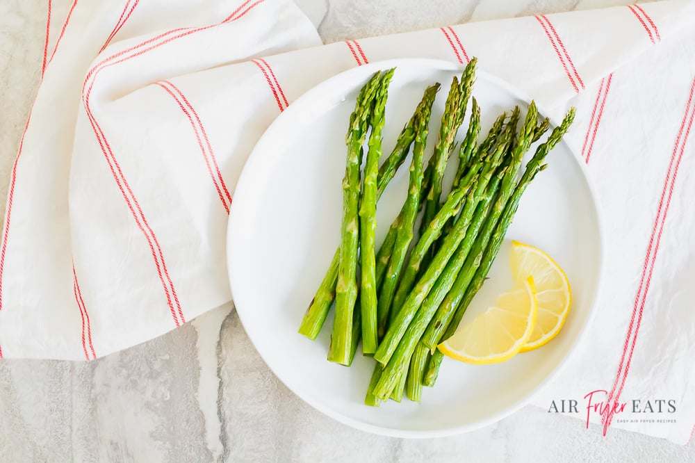 Cooked asparagus and lemon wedges on a white plate