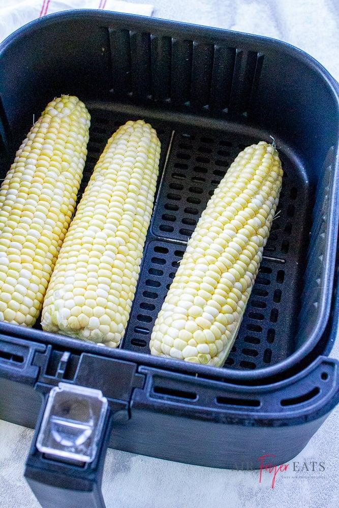 three uncooked ears of bi color corn in a black air fryer basket