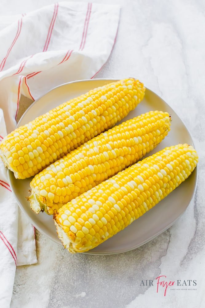 three ears of bi color corn on a white plate with a red and white napkin to the left