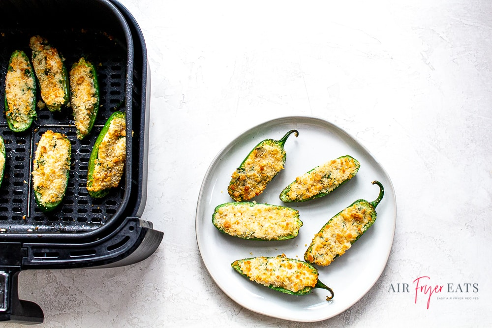 White plate with 5 air fried jalapeno poppers. To the left of the plate is a black air fryer basket with 5 cooked air fryer jalapeno poppers. This is set on a white back ground.