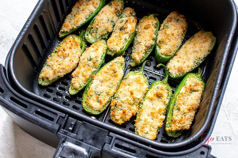 cooked golden brown topped jalapeno poppers in a black air fryer basket.