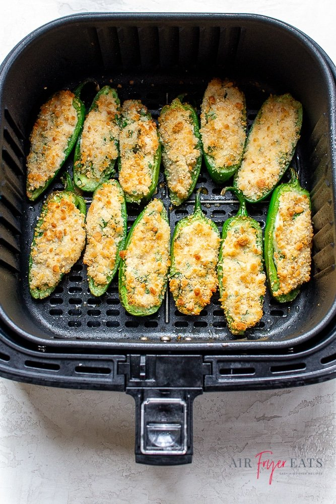 picture of bread jalapeno poppers in a black air fryer basket.