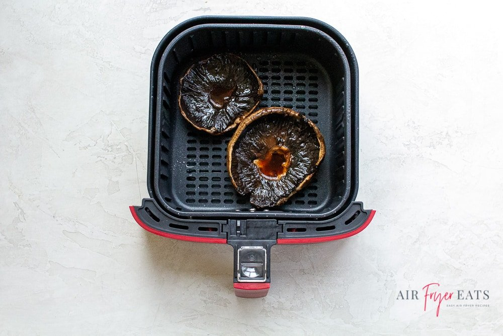 cooked portabello mushrooms in an air fryer basket