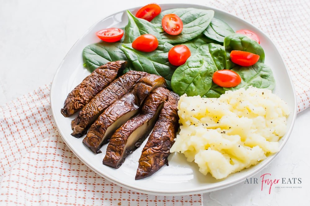 sliced portabello mushrooms with mashed potatoes and a side salad on a white plate