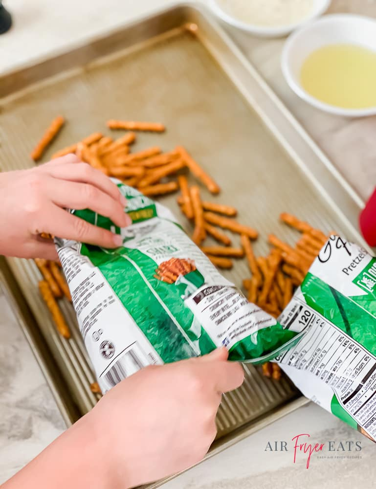 picture of two hands dumping a bag of rod pretzels onto a lipped baking sheet