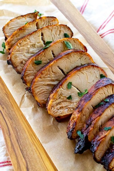 sliced turkey on a cutting board with parsley