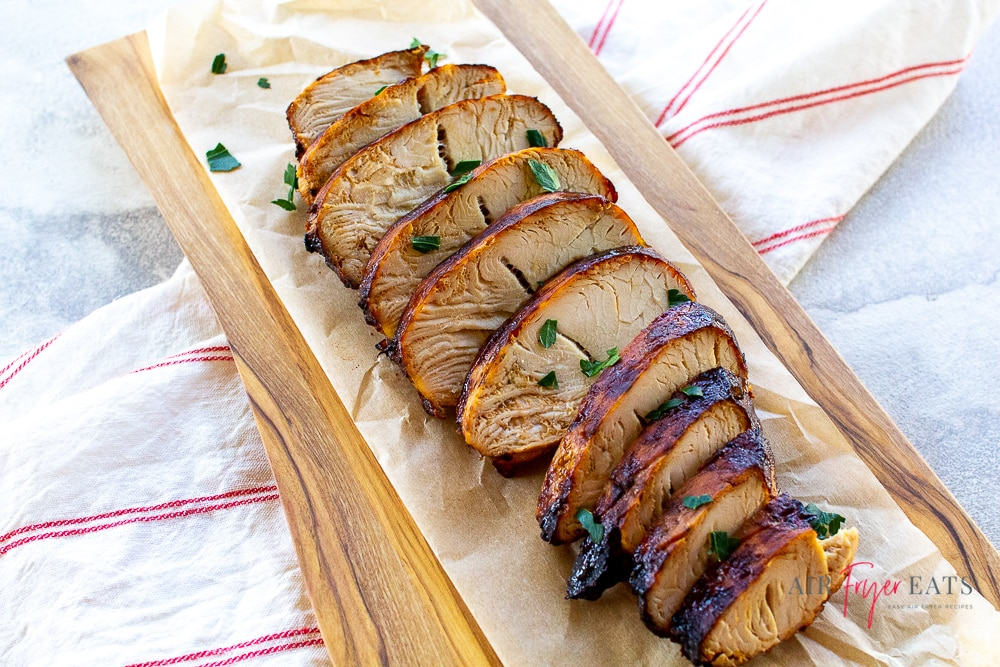 sliced turkey and parsley on parchment paper across and red and white striped towel