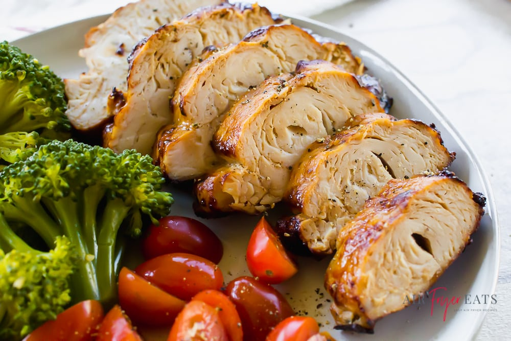sliced seasoned turkey breast on a white plate with cherry tomatoes and steamed broccoli