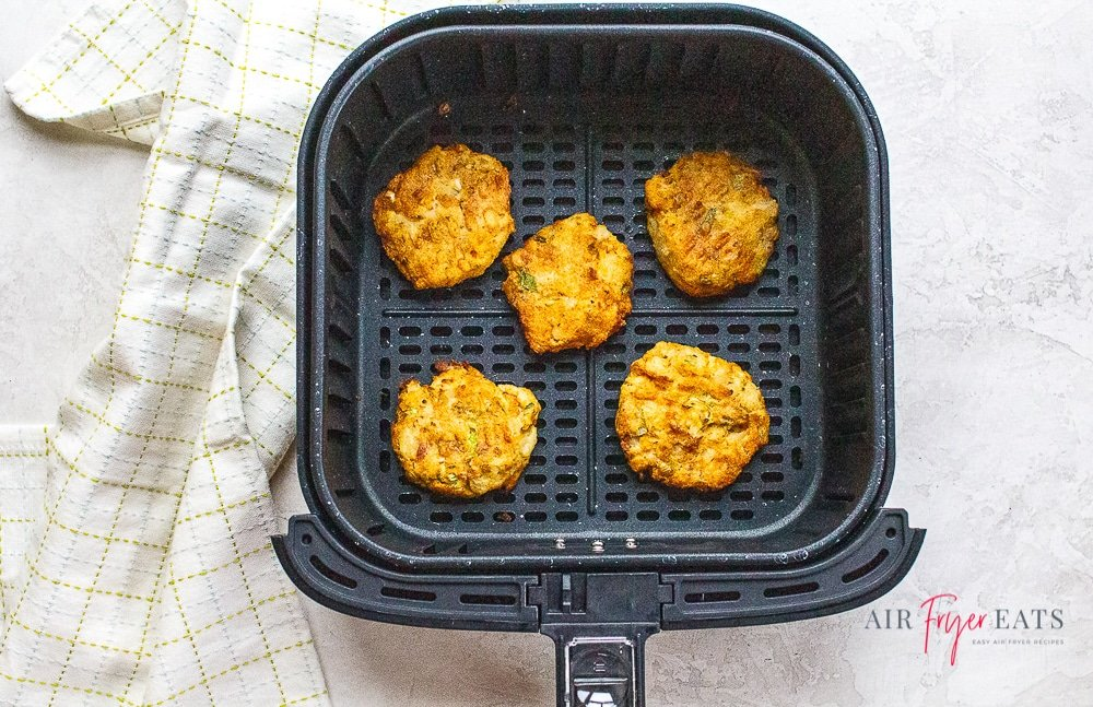 mashed potato pancakes in air fryer basket next to a white kitchen towel