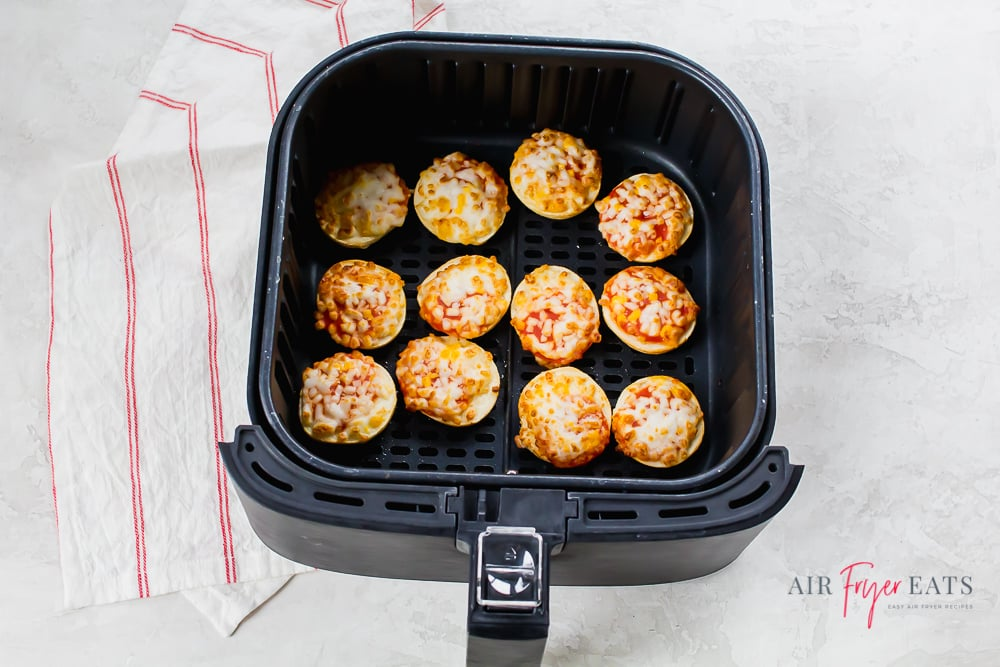 Overhead shot of cooked air fryer bagel bites in a black air fryer basket on a white back ground. There is a white and red striped napkin to the left of the basket.