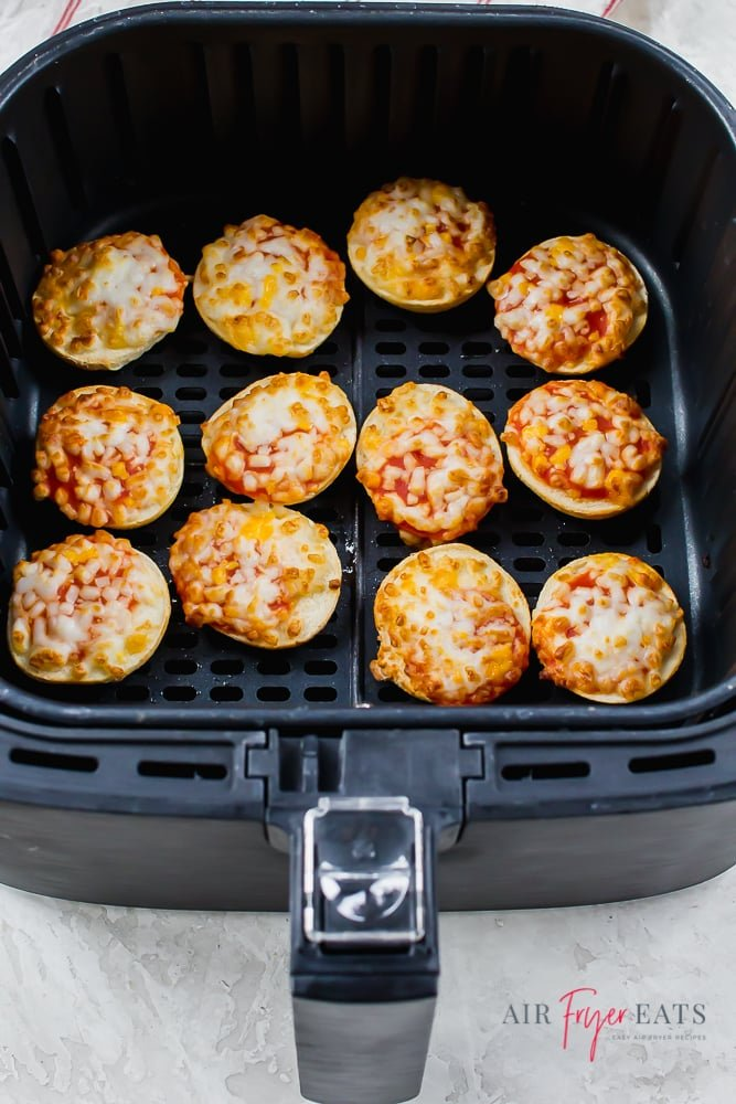 Cooked pizza bagel bites in black air fryer basket