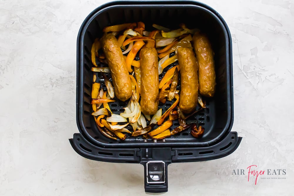 cooked brats, bell pepper, and onions in an air fryer basket