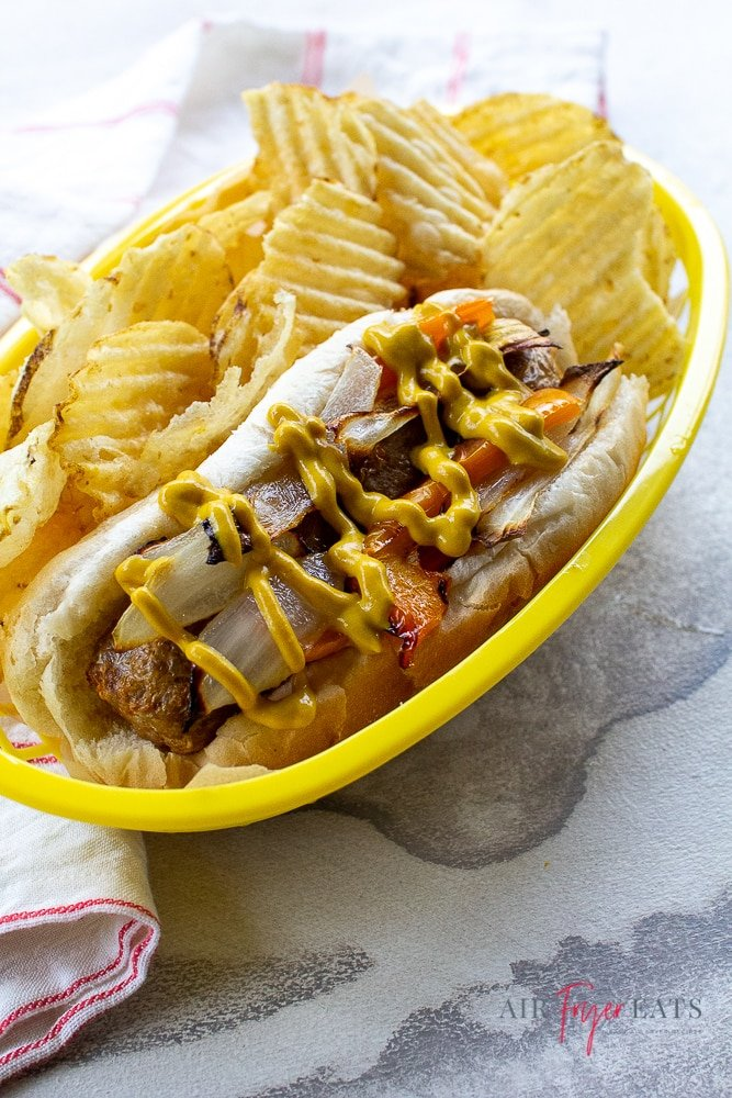 brats, bell peppers, and onions on a hot dog bun with chips on a yellow plate