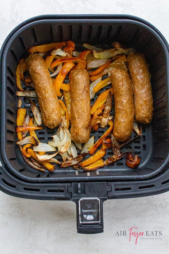 Cooked brats, bell peppers, and onions in an air fryer basket