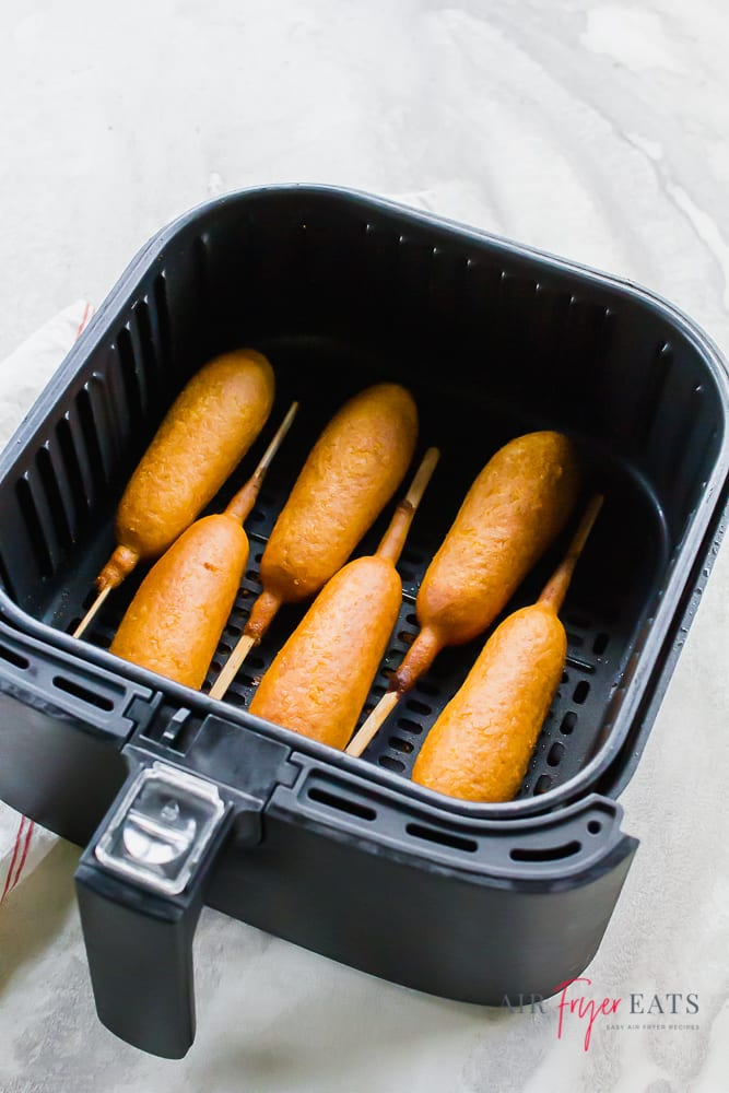 vertical picture of a black air fryer basket with corn dogs inside. White background.