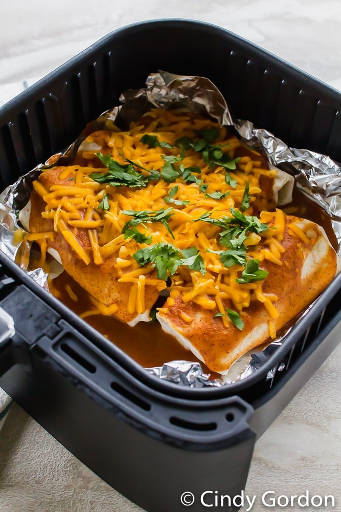 vegetarian enchiladas topped with shredded cheese and cilantro in an air fryer basket coated with aluminum foil