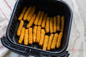 uncooked fish sticks in black air fryer basket