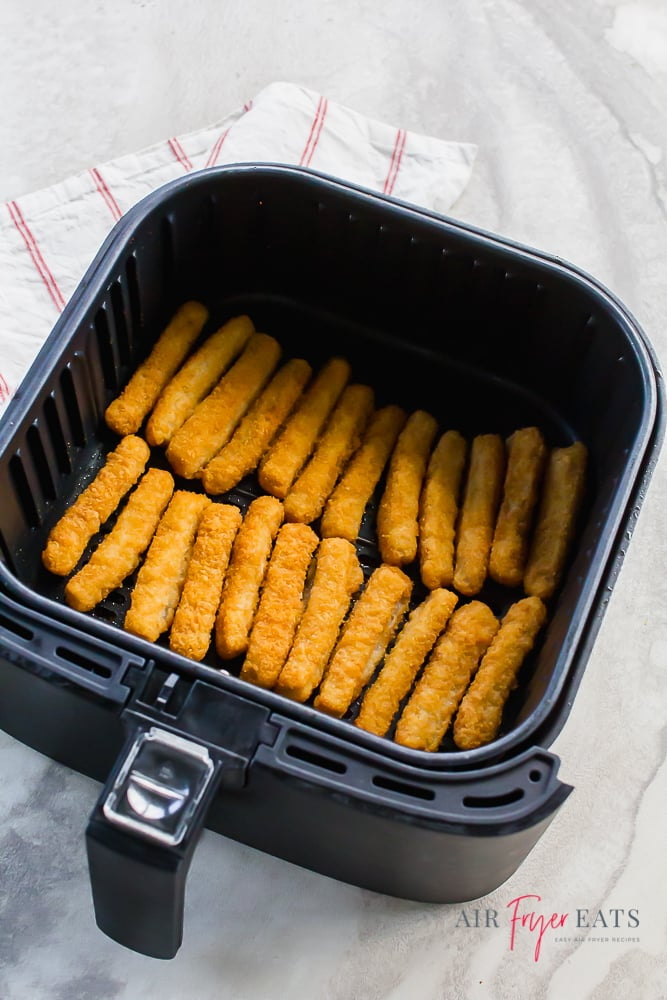 Black air fryer basket filled with breaded fish sticks on a white background. There is a white napkin with thin red stripes to the left of the air fryer basket.