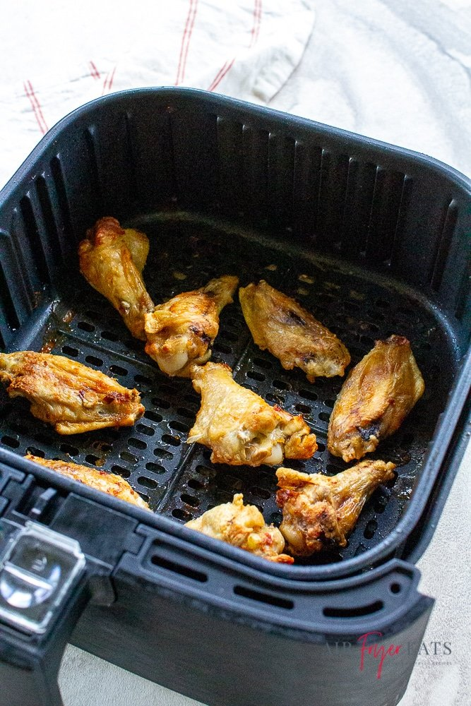 Vertical photo, showing a black air fryer basket with cooked chicken wings inside it. All on a white background with a white and red striped napkin to the left/top.