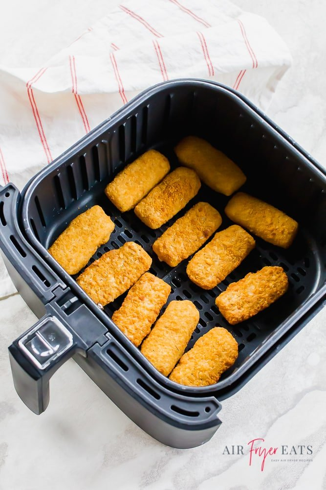 Overhead picture of mozzarella bites in a black air fryer basket with white/red napkin.