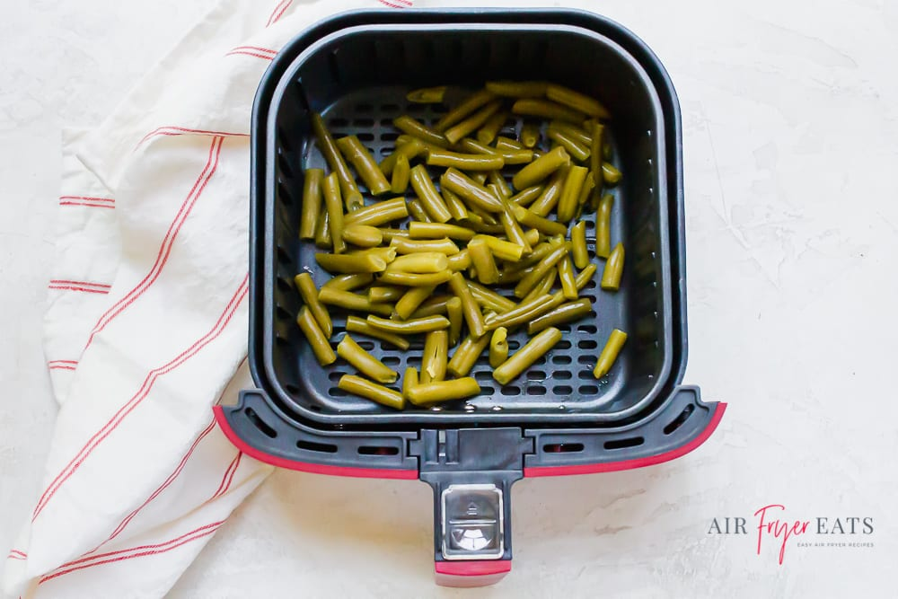 Air Fryer Green beans in a red and black air fryer basket