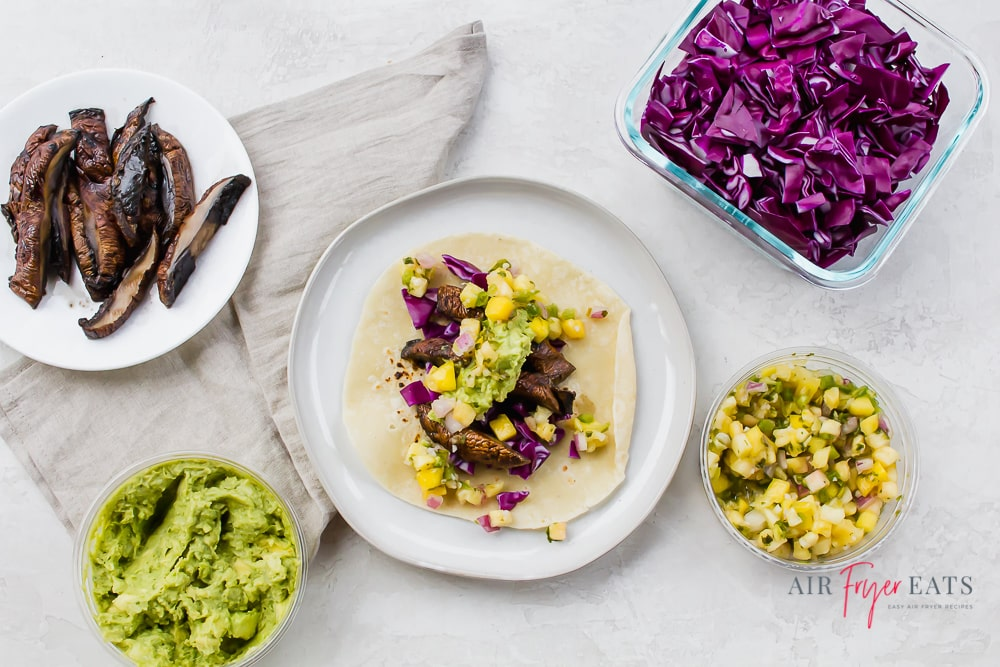 A mushroom taco surrounded by red cabbage, pineapple salsa, guacamole, and sliced portobello mushrooms