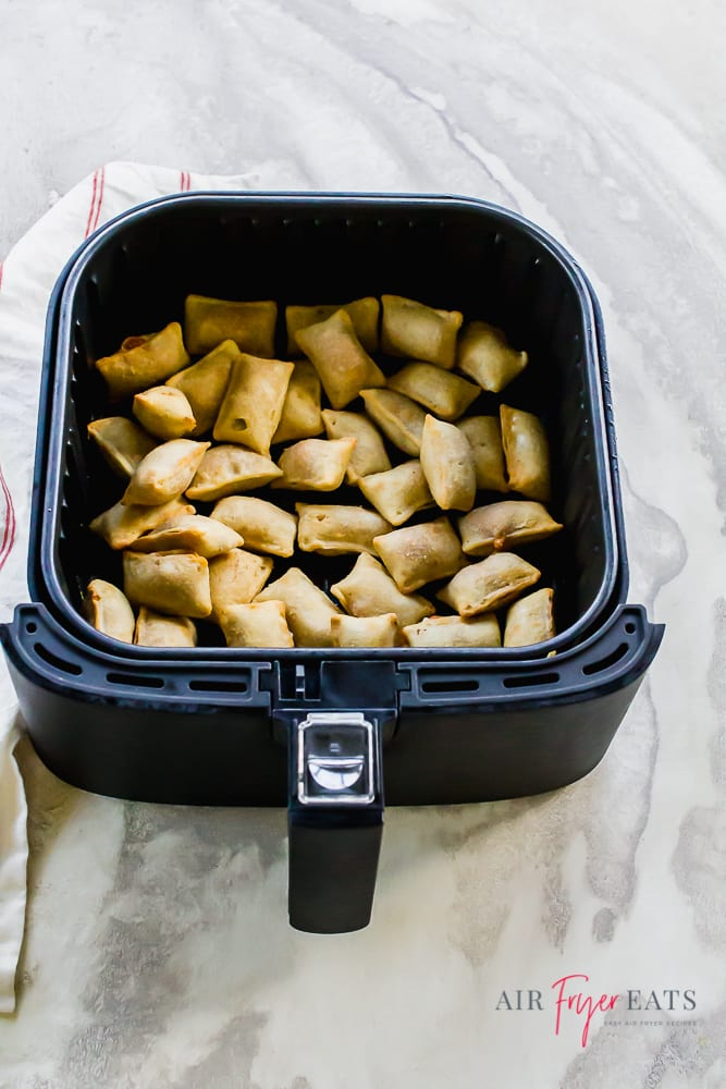 Vertical picture showing cooked pizza rolls in the air fryer basket. The basket is black. The pizza rolls are a golden brown.