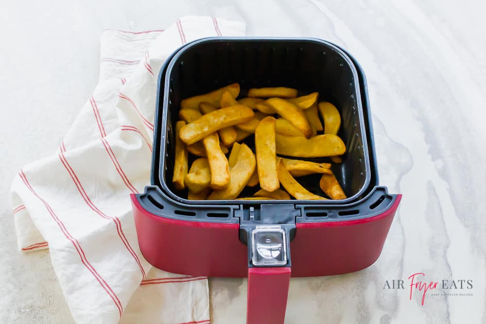 Horizontal picture with steak fries in a red and black air fryer basket set on top of a white background. There is a white napkin with thin red stripes to the left of the basket.