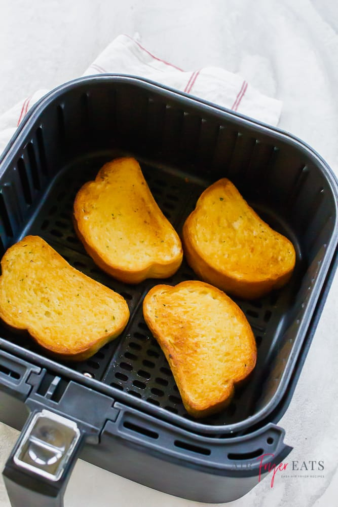Vertical photo of cooked texas toast in black air fryer basket on a white background. White napkin with thin red stripe to the top and left.