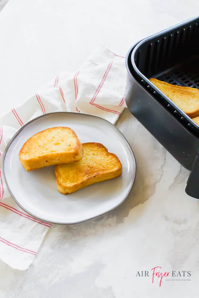 Vertical picture of cooked garlic toast on a white plate with a white napkin to the left. On the right you can see a black air fryer basket with garlic toast inside.