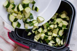 diced zucchini being added to an air fryer basket for cooking