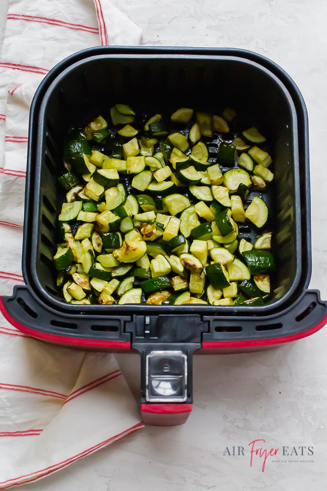 cooked zucchini in an air fryer basket with a red plaid towel