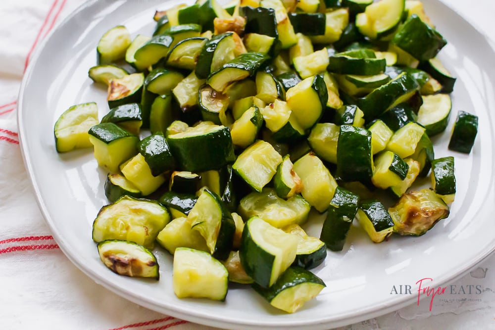 cooked zucchini on a white plate with a red plaid kitchen towel