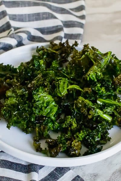 kale chips on a white plate with a blue striped kitchen towel on a marble countertop
