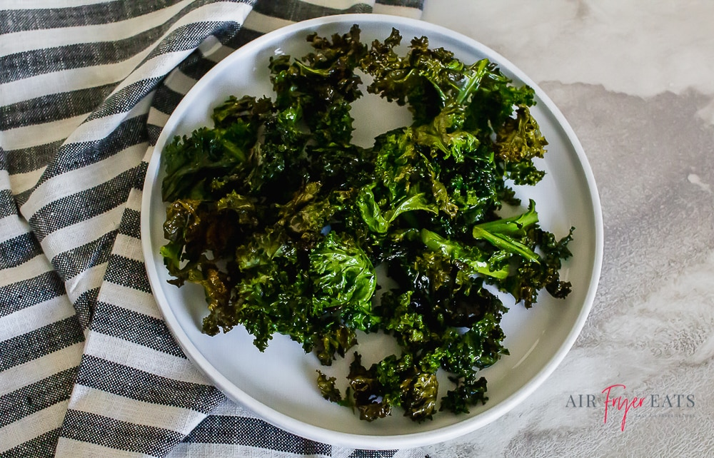 kale chips on a white plate with a gray striped kitchen towel on a marble countertop