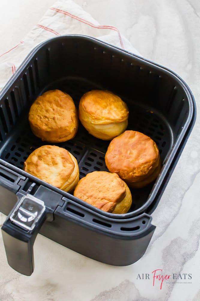 golden brown biscuits in black air fryer basket.