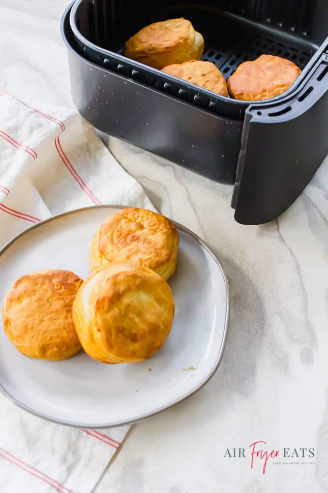 Vertical Image of air fryer biscuits on a white plate at the bottom of the picture and in an air fryer basket at the top of the photo.