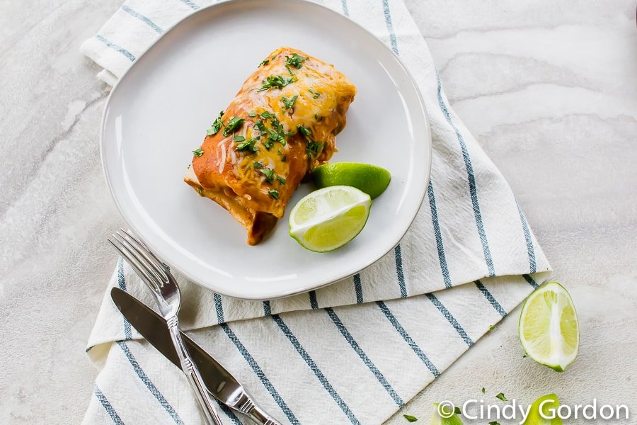 vegetarian enchiladas on a white plate with lime wedges on the side