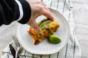 a hand squeezing lime juice over vegetarian enchiladas on a white plate with lime wedges